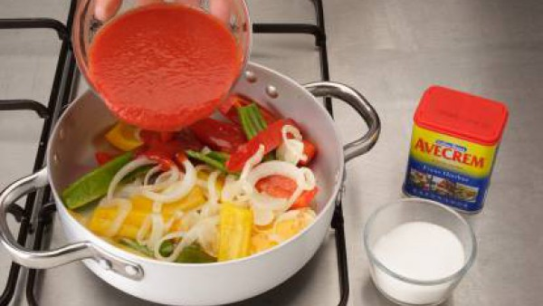 Incorpora el tomate triturado, el azúcar y sazona con Avecrem Caldo de Pollo.