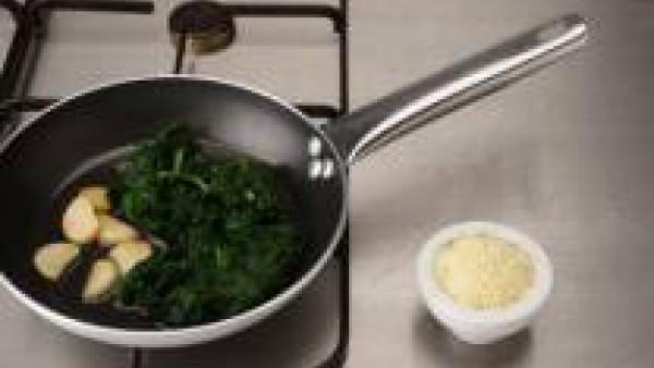 Incorpora las espinacas, remueve bien y apártalas del fuego. Retira el diente de ajo y espolvorea con la mitad del queso rallado. Mezclar otra vez y reserva.