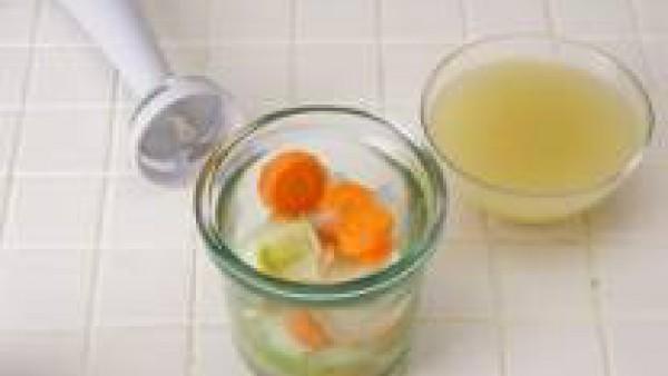 Tritura con la batidora, los puerros, la cebolla y 1 zanahoria con 1 cucharada de caldo.  Pasa la mezcla por el pasapurés y reserva. Corta el resto de las zanahorias en rodajas. Calienta el aceite en