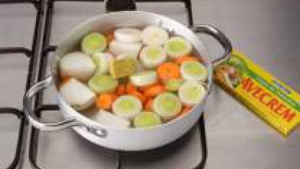 Raspa las zanahorias y limpia los puerros. Lávalos y ponlos en una cacerola con la cebolla pelada por la mitad. Cúbrelos con agua, lleva a ebullición, sazona con la  pastilla de Avecrem desmenuzada y