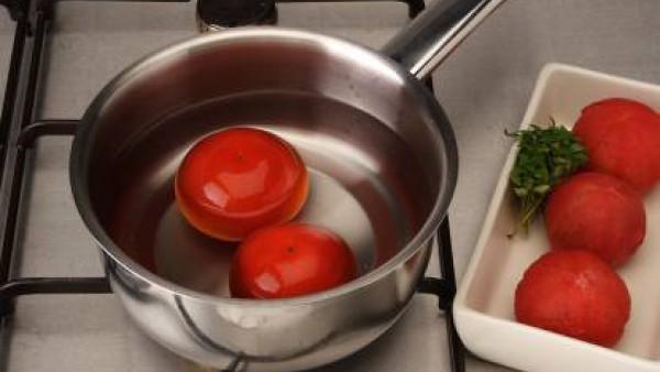 Precalienta el horno a 180ºC. Haz un corte en forma de cruz en la base de los tomates y escaldarlos durante unos segundos. Escúrrelos y deja que se templen.  Pélalos con cuidado de que no se deshagan