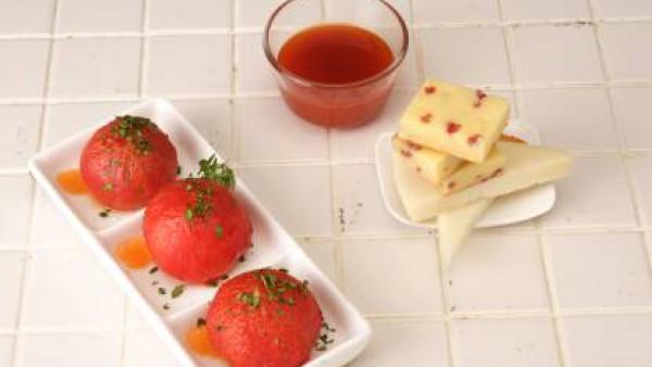 Dispón los tomates en una fuente de servir, riégalos con el fondo de cocción caramelizado y espolvoréalos con la sal gorda. Decora con las hojitas de albahaca y sírvelos acompañados de los quesos.