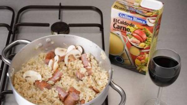 Calienta una cucharada de mantequilla con un poco de aceite en una cazuela de fondo grueso. Fríe las salchichas cortadas. Añade los ajos picados y la cebolla troceada. Deja dorar. Agrega las setas (pr