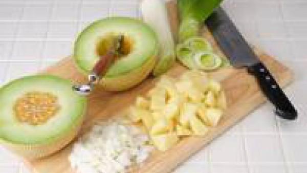 Corta el melón por la mitad, retira las semillas y filamentos con la ayuda de una cuchara y pélalo completamente. Reserva aparte un par de tajadas grandes para hacer las bolitas de la guarnición. Cort