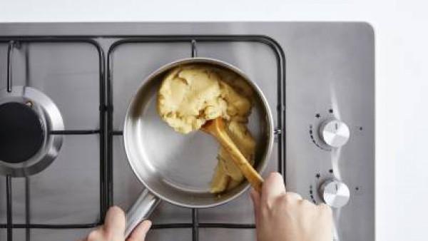 Mezcla con una cuchara de madera hasta obtener una pasta fina. Continúa removiendo hasta que la pasta se desprenda del cazo unos 3 minutos. Deja enfriar a temperatura ambiente unos 10 minutos. Añade l