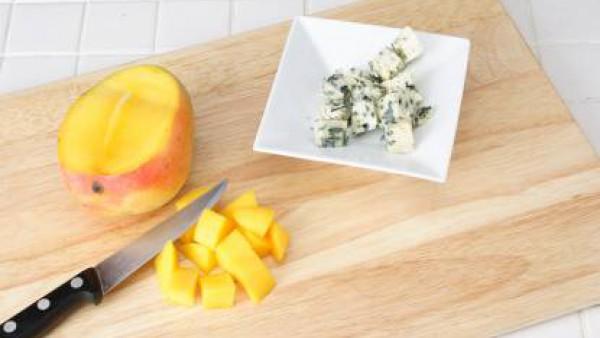 Pelar el mango, separar la pulpa del hueso y cortarla en dados. Cortar el queso azul en daditos.