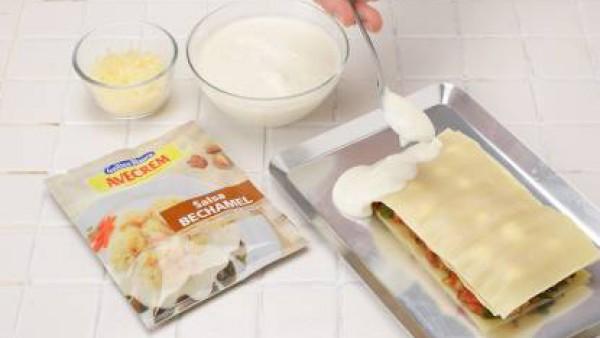 En una fuente apta para horno, extiende una capa de bechamel, y encima, una placa de lasaña. Incorpora encima los siguientes ingredientes en el mismo orden: carne picada, una capa de tomate frito, una
