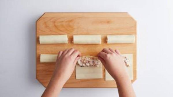 En una fuente apta para horno, disponer los rollitos de lasaña previamente rellenos de salchichas y un poco de masa de queso y huevo, que hemos preparado antes, cubrir con una capa de salsa tomate y e