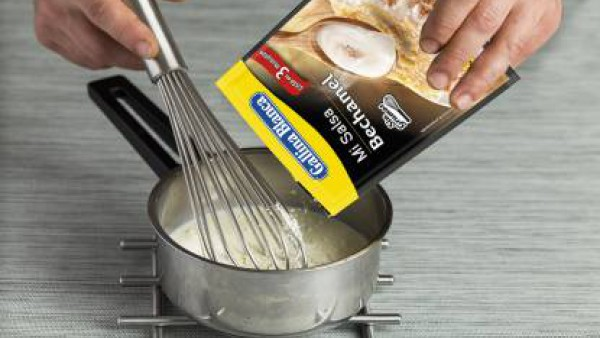 En la última placa, vierte unas cucharadas de bechamel, preparada con la leche, según las indicaciones del sobre y espolvorea con queso rallado. Gratina en el horno precalentado a 200ºC durante 10-12