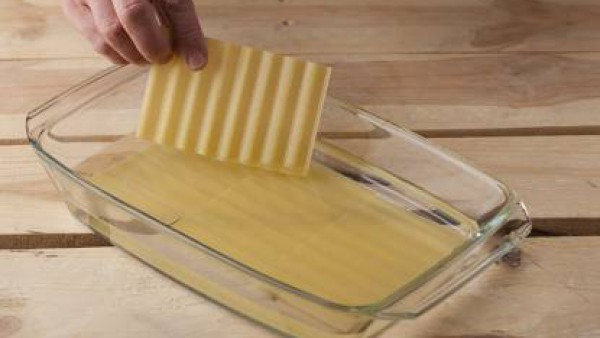 Hidrata las placas de lasaña según las instrucciones del envase. En una bandeja de horno pon un poco de mantequilla, una capa de pasta y una de sofrito, otra de pasta y el jamón york cortado en julian