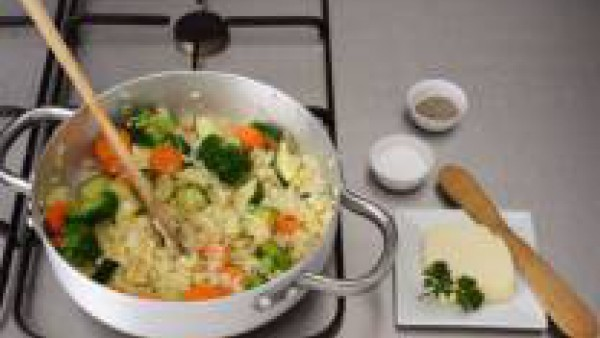 Vierte el caldo poco a poco y sin parar de remover. Cuando el arroz esté a media cocción, agrega las verduras reservadas y termina la cocción. Espolvorea con el parmesano rallado. Sirve de inmediato.