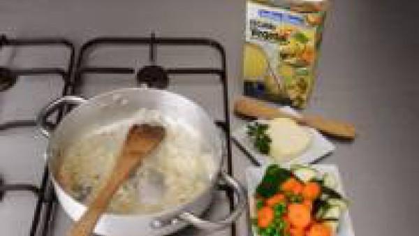 En una cazuela de fondo grueso, calienta 1 cucharada de mantequilla y rehoga la cebolla picada, cuando esté dorada incorpora el arroz y saltea, riega con el vino y condimenta con el curry.