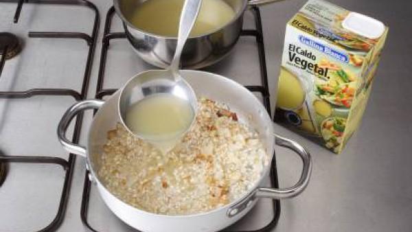 Calienta la mantequilla en una cazuela y rehoga el sofrito de cebolla, añade el ajo picado y deja dorar. Agrega el arroz y dóralo sin dejar de remover. Vierte un vaso del caldo y cuece el arroz durant