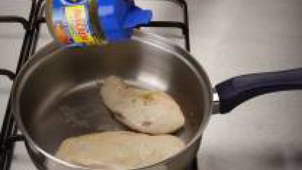 Corta la zanahoria, el calabacín y el pimiento rojo en tiras finas y reserva. Parte por la mitad las pechugas de pollo y sofríelas ligeramente en una cazuela con el aceite y espolvoreadas con finas hi