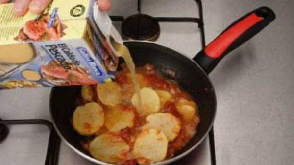 Añade los pimientos asados, las patatas a ruedas y el caldo, cuece unos 15 minutos.