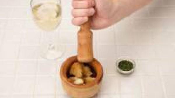 Mientras en un mortero pica los ajos que hemos reservado, la rebanada de pan frita, las almendras y el perejil, cuando esté dilúyelo con el vino.