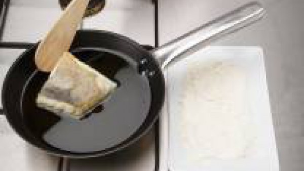 Enharina el bacalao y fríelo en una sartén con 4 cucharadas de aceite caliente durante 2 min.
