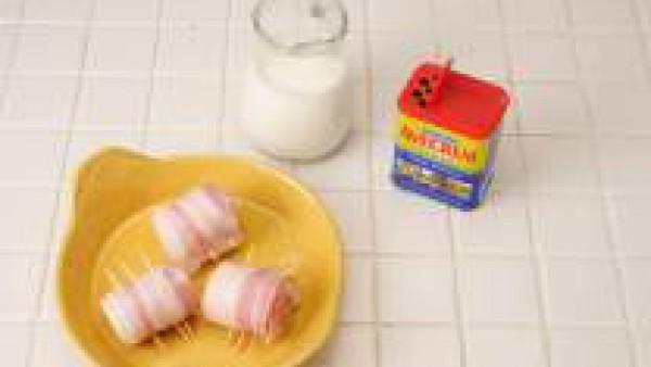 Dispón los rollitos en una fuente de horno engrasada, riega con el vino y baña con la nata líquida.