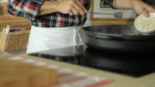 En la misma cazuela pocha ligeramente la cebolla picada gruesa, el ajo picado y el bacón cortado en dados. Lava y corta la parte terrosa de los champiñones. Corta en cuartos e incorpora al guiso, pros