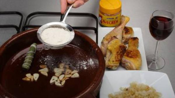 En una cazuela calienta aceite y dora los trozos de pollo, reservándolos. En la misma grasa, añade los ajos a láminas. Espolvorea con un poco de harina, rocía con el vino y agrega los trozos de pollo