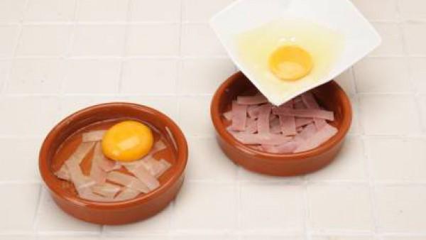 Precalienta el horno a 200º. Prepara una cazuelita de barro pequeña. En el fondo de la cazuelita coloca unas tiras de pimiento rojo, una cucharadita de aceite de oliva y unas tiras de jamón cocido. En