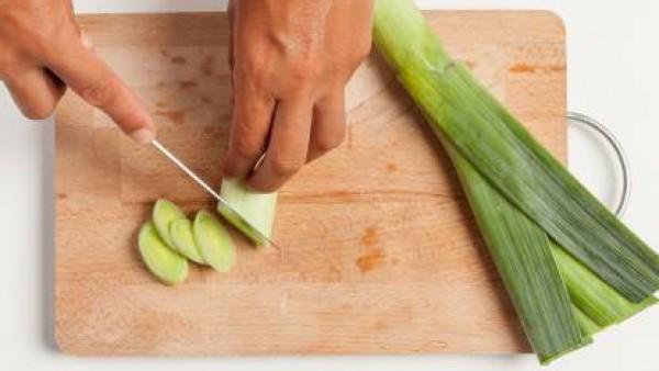 Por otra parte, corta los puerros en tiras finas y fríelas en una sartén con un poco de aceite de oliva hasta que se doren ligeramente. En una sartén antiadherente dora un diente de ajo y una vez dora