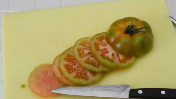 Corta el tomate por la mitad en sentido perpendicular. Presiona para quitarle las semillas, sala un poco y deja invertido para que se escurra. Luego calienta el aceite en una sartén, echa el tomate co