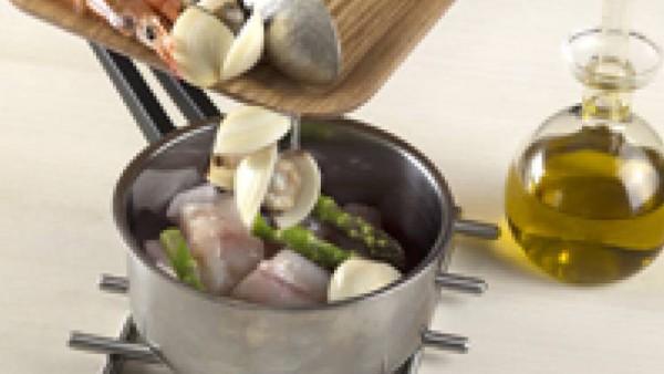 Tapa la sartén y deja cocer unos 2 minutos. Gira el pescado y coloca las gambas para que se sumerjan en la salsa. Deja cocer 5 minutos más e incorpora las almejas.