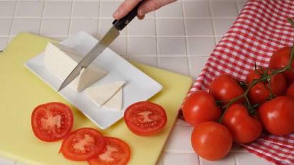 Lava los tomates y córtalos a rodajas. Colócalos en el fondo del plato. Pon las sardinas y el queso a trocitos por encima. Aliña el plato con el aceite de albahaca y la tapenade.