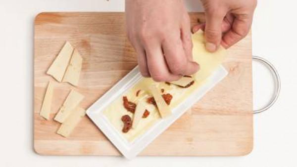 Extiende las láminas de la Lasaña Fácil el Pavo los platos y alterna la pasta con el queso de vaca y los tomates y el Tomate Frito Gallina Blanca. Termina con una capa de pasta, queso parmesano rallad