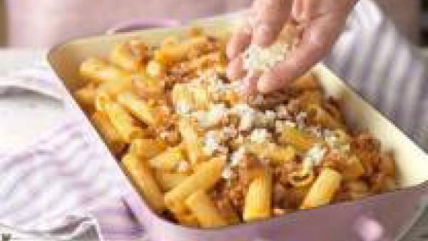 Remueve para que quede todo bien mezclado y pon los macarrones en una bandeja de horno. Espolvorea con el queso rallado y gratínalos bajo el grill del horno hasta que la superficie tenga un bonito col