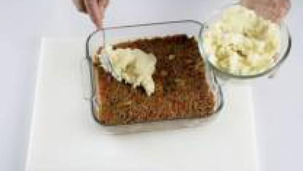 Echa por encima el puré de patatas que tenías reservado y repártelo sobre la carne hasta que quede bien plano.