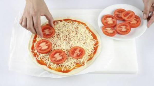 A continuación añade los tomates cortados en rodajas de forma uniforme por encima del queso.