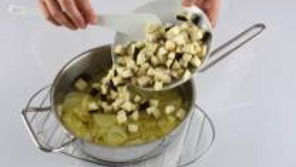 Pela y corta la cebolla en tiras finas y la patata en rodajas. En una cazuela con una cucharada de aceite de oliva, pon a pochar la cebolla junto con la patata. Pela y corta la berenjena a daditos peq