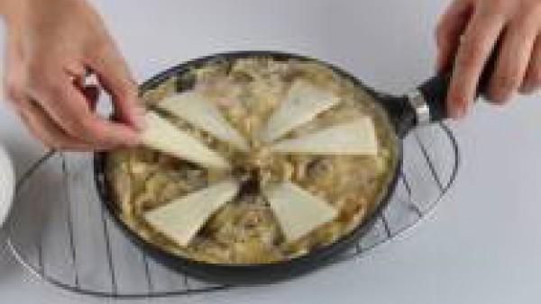 Añade el queso cortado en cuñas finas por toda la superficie de la tortilla y dale la vuelta con la ayuda de un plato llano. Deja que se termine de cocer la tortilla y sírvela aun caliente.