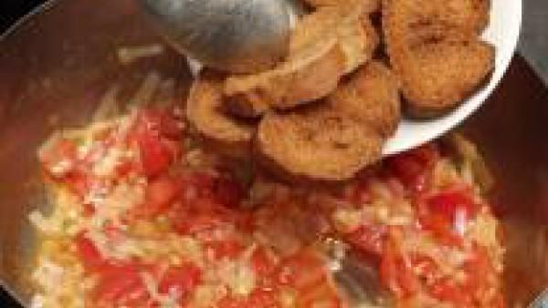 Una vez rehogadas las verduras, echa las rebanadas de pan frito y moja con el caldo de pescado.