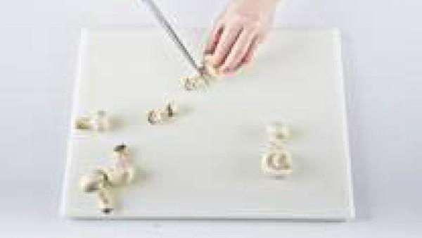 Corta el pie de los champiñones, ponlos en un colador y lávalos bajo el grifo. Sécalos bien con papel absorbente y córtalos en láminas finas.