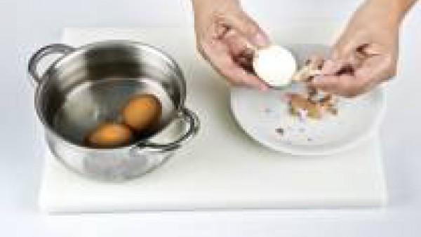 Pon los huevos en el agua hirviendo y deja que cuezan durante 10 min. Luego escúrrelos, enfríalos bajo el grifo de agua fría y pélalos con cuidado. Córtalos por la mitad y separa la clara de la yema.