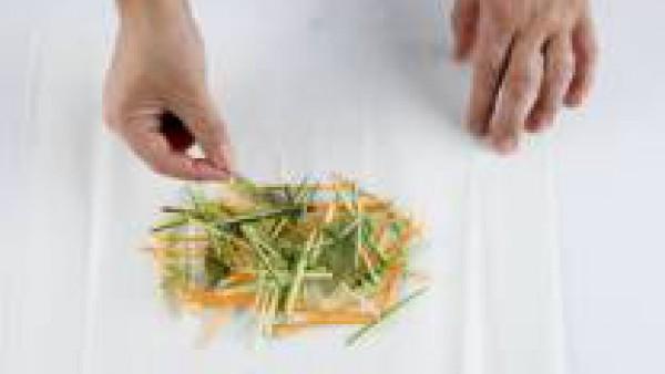 Corta las verduras en tiritas finas. Corta el limón en rodajas y los ajos en láminas finas. Pon las verduras y las hierbas frescas sobre una hoja de papel de horno.