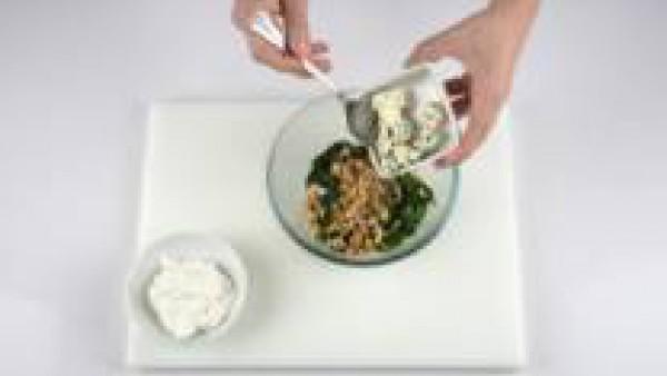 Trocea las nueces y el queso azul y échalos en el bol de las espinacas. Añade el queso cremoso para untar, la pimienta y remueve bien. Desenrolla el paquete de pasta filo, saca una hoja y guarda el re