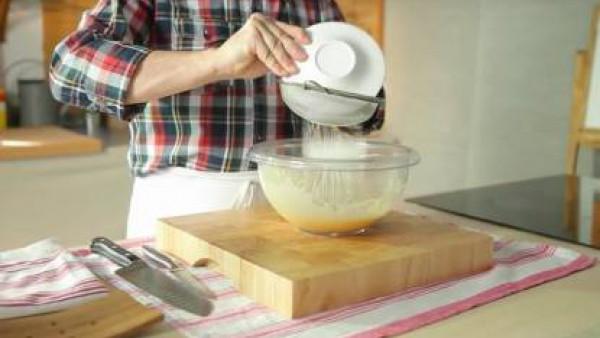 Aparte, bate las yemas y el huevo entero con el azúcar. Mézclalos hasta que obtengas una pasta blanca.  Pon la maicena dentro de un colador e incorpórala, despacio y en forma de lluvia dentro de la me