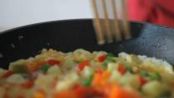 Remueve el huevo ligeramente con un tenedor o espátula y, cuando la masa de huevos empiece a separarse de los lados, redondea la tortilla con el tenedor.
