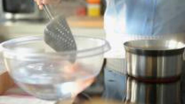 Prepara el relleno de las patatas: pon una cazuela ancha a calentar a fuego lento con una parte del aceite de oliva y los chalotes pelados y picados muy fino. Déjalos rehogar a fuego lento hasta que s