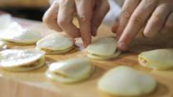 Dispón una lámina de patata. Colócale encima una parte el relleno y tápalo con otra lámina de patata. Enharina las patatas, pásalas por clara de huevo batida y fríelas en una sartén a fuego medio, con