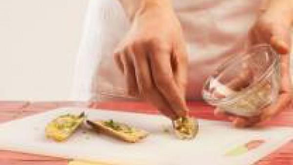 Rellena las navajas con la masa y colócalas en una bandeja de horno. Mójalas de nuevo con un poco de caldo y cuécelas en el horno durante 10 minutos a 180 °C. Cuando estén doradas, retira las navajas