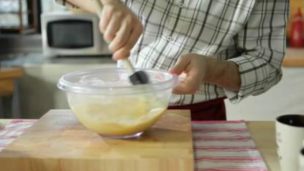 Moja los ingredientes secos con media taza americana de agua y tres cuartos de taza americana de leche. Ahora remueve con una espátula para que la masa se homogenice y tome cuerpo.