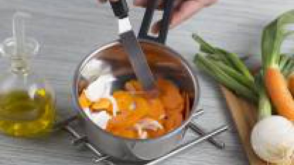 Pela y corta la zanahoria en rodajas finas y añádelas al sofrito de cebolla, deja que se ablanden unos 5 minutos, añade el Caldo Casero Suave de Pollo Gallina Blanca, la cúrcuma, el comino y deja coce