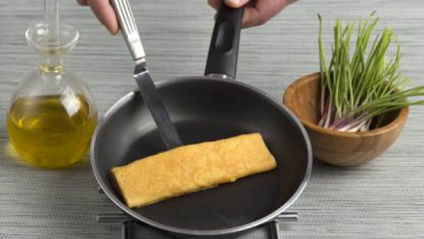 Pon al fuego una sartén con un chorrito de aceite de oliva. Bate el huevo, añade una pizca de sal y haz una tortilla plana. Córtala en tiras finas.