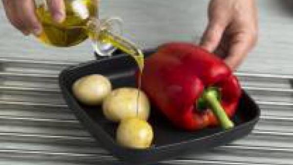 Pon a cocer en el horno a 220 ºC los pimientos rojos y las patatas enteras.
