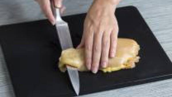 Abre las pechugas de pollo por la mitad y rellénalas con una loncha de queso, una lámina de jamón y unas tiras de pimiento rojo asado. Salpimienta y ata las pechugas de pollo con la ayuda del hilo de